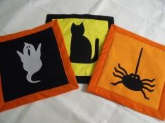 "These are samples of three halloween potholders/hotpads designed by Carol Murphy, Sept. 2009; she used an 8 1/2"" square block; insul-bright insulated batting; and a yard of bias tape, plus the adorable halloween appliques"